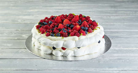Meringue pavlova wreath cakes with whipped cream and fresh berries, close up Stock Photo