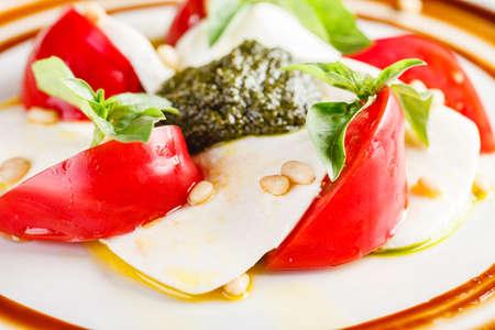 Caprese salad with mozzarella, tomato, basil and pesto arranged on white plate