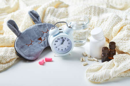 Sleeping mask, alarm clock, earplugs, essential oils and pills. Healthy night sleep creative concept. Good night, sleep hygiene, insomnia