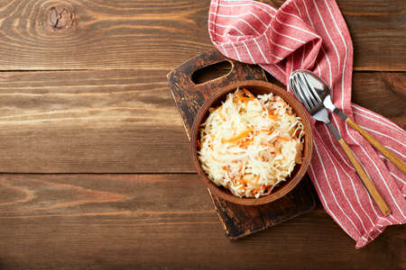 Sauerkraut, fermented cabbage with carrots in bowl on wooden background with copy space. Superfoods for support the immune system. Top view, flat lay