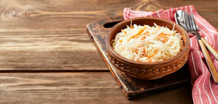 Sauerkraut, fermented cabbage with carrots in bowl on wooden background with copy space. Superfoods for support the immune system.