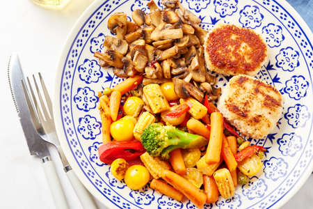 Mixed vegetables of carrots, broccoli, baby corn, bell peppers, roasted champignons and two chicken patties in breadcrumbs Standard-Bild