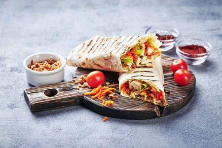 Eastern traditional shawarma with chicken and vegetables, Doner Kebab with sauces on wooden cutting board. Fast food. Eastern food. Standard-Bild