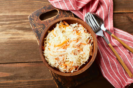Sauerkraut, fermented cabbage with carrots in bowl on wooden background. Superfoods for support the immune system. Top view, flat lay Standard-Bild