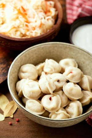 Traditional Russian pelmeni dumplings with sour cream and sauerkraut with sour cream over wooden background.