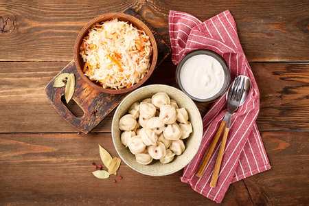 Traditional Russian pelmeni dumplings with sour cream and sauerkraut with sour cream over wooden background. Top view, flat lay.