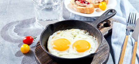 Fried eggs. Fried eggs from two eggs in cast-iron pan with cherry tomatoes, toast. Sunny morning breakfast concept banner Standard-Bild
