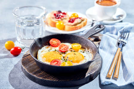 Fried eggs. Fried eggs from two eggs in cast-iron pan with cherry tomatoes and microgreens, toast and cup of coffee. Sunny morning breakfast concept