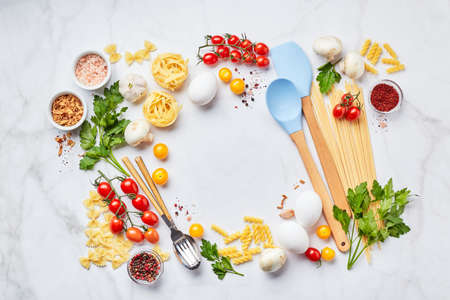Food background with place for text, with different kinds of pasta, tomatoes, herbs, mushrooms, eggs, seasonings scattered on light marble background, top view. Italian cuisine concept