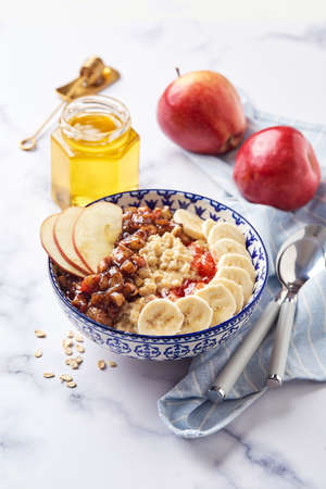 Oatmeal porridge with caramelized apples with cinnamon, banana, grated strawberries and honey on light marble background, close up