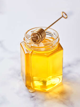 Glass jar with floral liquid honey and metal honey spoon on light marble background. Alternative sugar substitute, cold remedy and body strengthening, superfood Standard-Bild