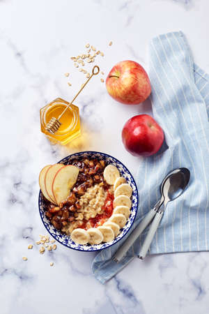 Oatmeal porridge with caramelized apples with cinnamon, banana, grated strawberries and honey on light marble background, top view. Standard-Bild