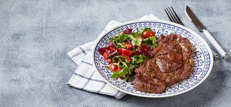 Grilled steaks and vegetable salad on light background. Table setting, food concept.