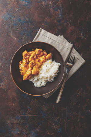 Tasty dinner with Chicken in coconut milk curry sauce with rice in dark dish on dark background, top view. Asian style. Stock Photo