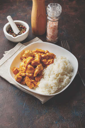 Tasty dinner with Chicken in coconut milk curry sauce with rice in white dish on dark background, top view. Asian style. Stock Photo