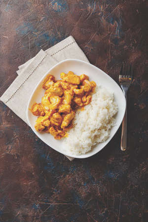 Tasty dinner with Chicken in coconut milk curry sauce with rice in white dish on dark background, top view. Asian style. Reklamní fotografie
