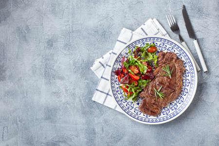 Grilled steaks and vegetable salad on grey