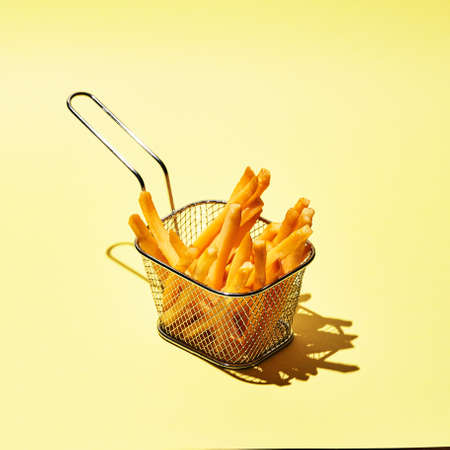 Tasty french fries in metal wire basket on yellow