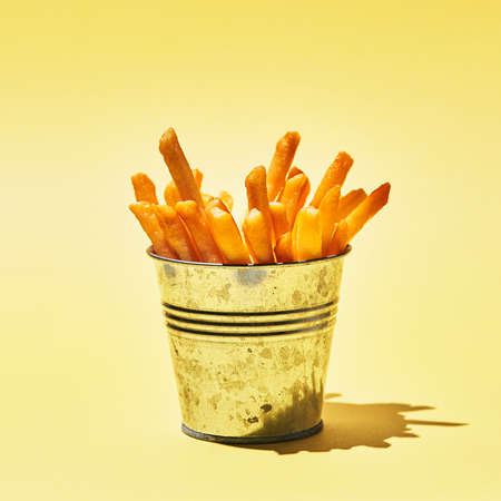 Tasty french fries in metal bucket on yellow table in sunlight. Stock Photo