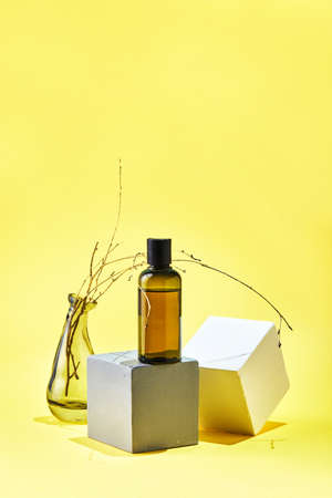 Glass Mock up bottle of shampoo or conditioner of body care cosmetics on geometric shapes and dried branch on yellow background. Natural eco friendly organic cosmetic spa beauty concept.