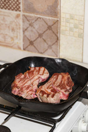 Two fresh raw meat of beef steak Prime Black Angus Chuck roll steak grilled in pan on gas stove.