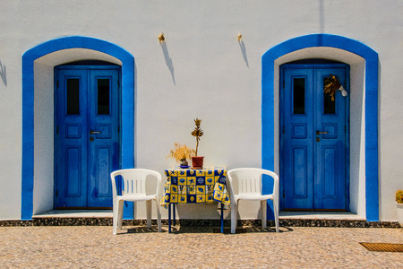 Symmetry of two blue doors, two white chairs and one yelloy table between