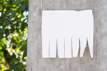 Empty white paper posted on a cement street post and marked with your own message. Blank advertisement with cut slips. mockup Stock fotó