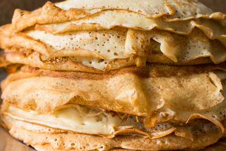 Stack of English pancakes on a round white plate on a black background. Shrove Tuesday, Pancake Day in Britain. Appetizing russian pancakes for Maslenitsa carnival (Shrovetide). Close up Standard-Bild