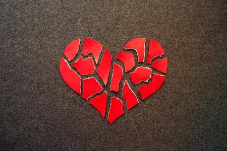 Paper red broken heart on dark felt background. Mosaic paper heart from pieces. Cracked heart symbol. Broken love concept. Stock Photo