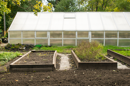 Greenhouse and plowed flowerbeds in the park. Glass greenhouse and site for growing of seedlings, bushes and flowers. Rise bedding plants for city park. Stock Photo