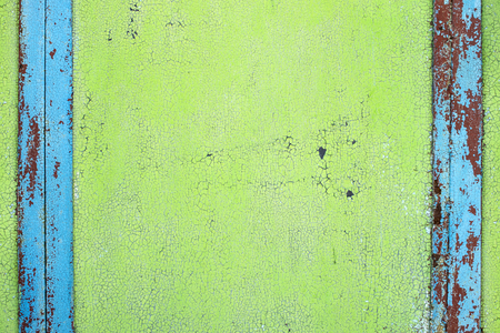 Texture cracked old paint, bright green background with vertical blue stripes on the sides Stock Photo