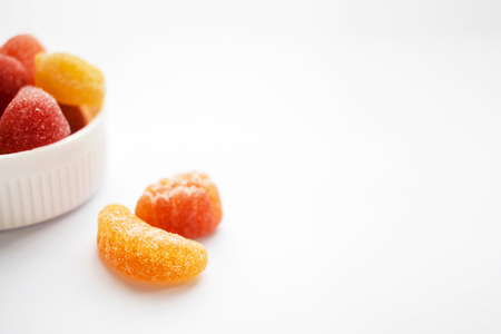 Children colorful gummy vitamins on white background. Multivitamin soft jelly candies in form of different kind of fruit. Nutrition supplement concept. Close up. Selective focus