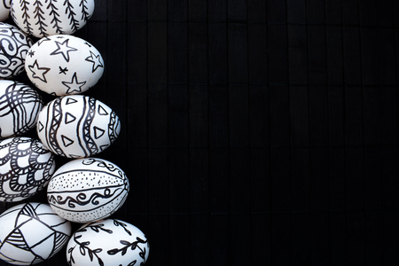 Easter eggs with the hand-drawn different doodle patterns on a black background. Pascha eggs with doodle unusual décor and copy space. Happy  Easter decor in a modern style