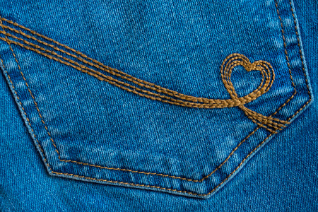 Embroidery in the shape of a heart on a denim pockets. Blue denim background with brown stitch