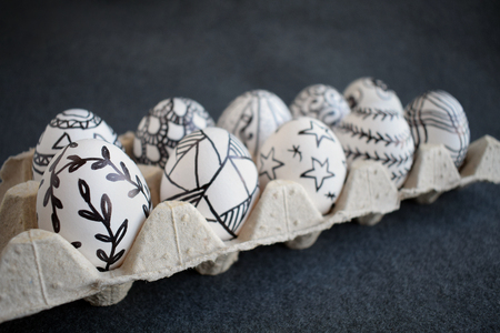 Many easter eggs with doodle graphic patterns in carton packing on a dark background. Pascha eggs with  black and white hand drown pattern. Happy easter concept. Selective focus 写真素材