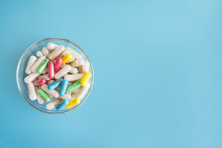Colorful pills and medicines in glass plate on blue background. Different pills and another drugs capsules for illegal doping manipulations. Pharmacy antibiotic and antidepressant.