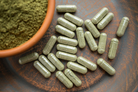 Supplement kratom green capsules and powder on brown plate. Herbal product alt-medicine kratom is opioid. Home alternative pain remedy, opioid addiction, dangerous painkiller, overdose. Close up. Sele 写真素材