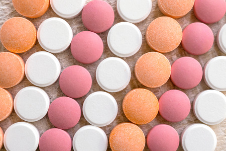 White, pink and orange tablets stripes background. Different Antacids medications help neutralize stomach acid. Antacid Oral : Uses, Side Effects, Interactions, Risks, Warnings Фото со стока