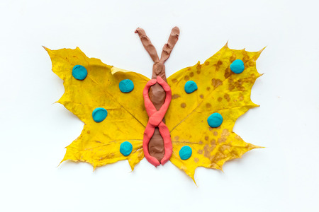 Fall Leaf Crafts for Kids. Craft handmade butterfly from dry yellow leaves and red, brown and blue plasticine, modeling clay. Ideas for kids arts and crafts isolated on white