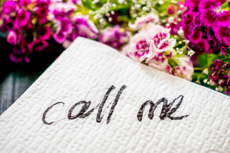 The inscription CALL ME on a white napkin left on the table in a cafe. Text call me on a background of pink flowers and lipstick. Dating, Love meeting