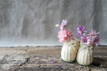 Delicate bouquet of purple and pink wildflowers in decorative mini straw shoes. Flower arrangement on a wooden background with copy space