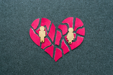 Breakup, divorce, failed relationship concept. Broken, mosaic, pieces pink heart with wooden figures of man and woman on a gray background.