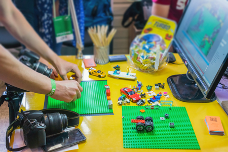 KROPIVNITSKIY, UKRAINE – 12 MAY, 2018: Stop motion animation process with Lego details and toy cars. Mens hands expose stop motion elements to create animations using a DSLR camera
