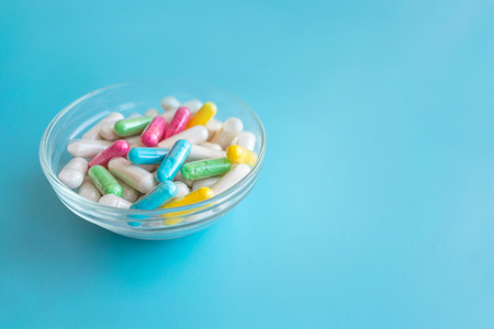 Nootropics, smart drugs, cognitive enhancers, compounds enhance brain function, Improve memory, cognitive and particularly executive functions. Multicolored capsules in female hand on blue background Stock Photo