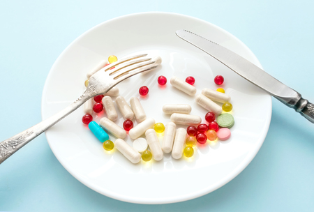 Many different weight loss pills and supplements as food on round white plate with fork and knife. diet pills and supplements, prescription weight loss drugs, appetite suppressants for dieting concept