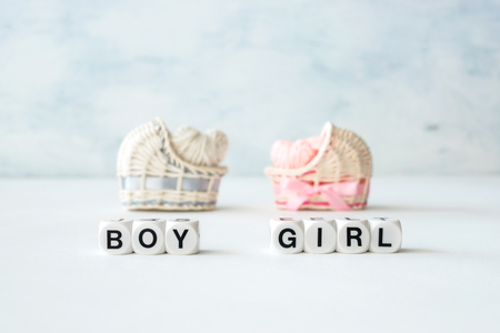 Baby shower ideas for a girl and boy party. Pink and blue decorative straw cradles with thread hearts and text BOY or GIRL. Standard-Bild