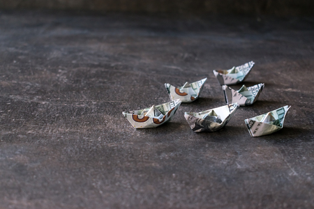 US Dollar paper boat on dark background. Many Ships from a money, Origami paper boats from dollars banknote on dark table. Financial, business concept. Selective focus