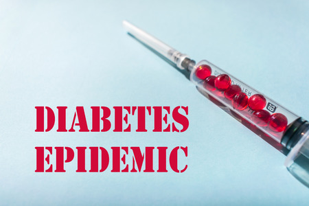 Diabetes epidemic, heart attacks and strokes. Type 1,2 diabetes. Medical concept: syringe with needle and red capsules inside and red words DIABETES EPIDEMIC on blue background