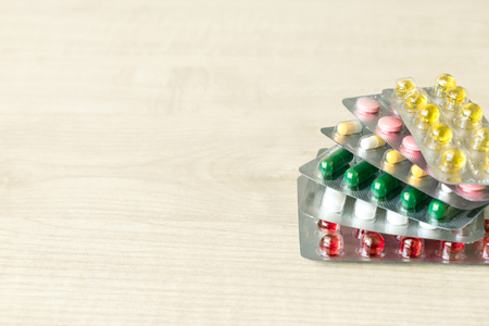 Pharmaceuticals antibiotics pills capsule medicine.  Stack  of different colorful antibacterials pills and capsule on wooden background Фото со стока