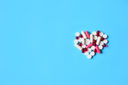 White and red various pills and capsules in heart  shape on blue background. Concept medical treatment, Medicine for diabetes, heart diseases and High blood pressure.